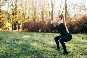 chica delgada realiza sentadillas mientras hace ejercicio al aire libre foto