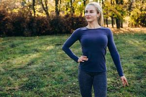 Slim girl posing in a sports suit outdoors. photo