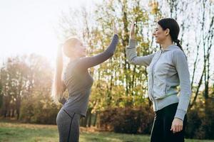 Chicas jóvenes dando cinco el uno al otro mientras hacen ejercicio al aire libre foto