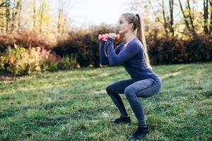Beautiful woman with dumbbells making morning exercises outdoor. Sport and health concept photo