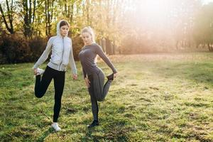 Two cute girlfriends do stretching before training outdoors. photo