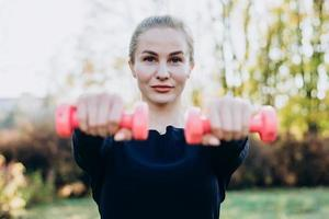 Beautiful young girl holding dumbbells stretched out in front of her. photo