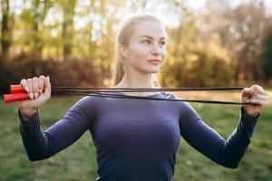 entrenando en el parque, niña sosteniendo una cuerda para saltar. foto