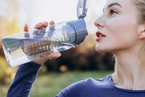 fitness en el parque, niña bebe agua de una botella, de cerca. foto