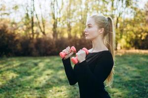 Profile of slim girl with dumbbells outdoors. Fitness in park. photo