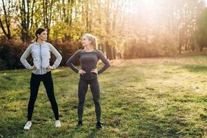 dos amigas están haciendo ejercicios en la naturaleza, mirándose. foto