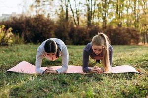 dos amigas están haciendo tabla de fitness en el parque. foto