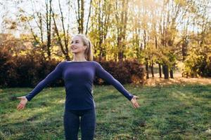 Beautiful smiling girl at morning gym in the park, looking away with arms extended. photo