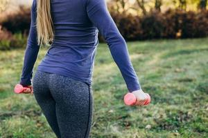 Closeup of buttocks girl holding dumbbells in fitness gym in park. photo