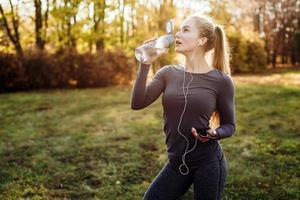 Fitness in the park, girl drinking water, holding smartphone and headphones in her hand. photo