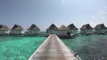 andando em passarela de madeira com bangalô e um lindo oceano se nas maldivas video