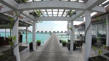 Caminando por la pasarela de madera con bungalow y hermoso océano se en maldivas video