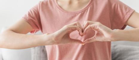 mujer haciendo las manos en forma de corazón, amor, seguro médico del corazón, responsabilidad social, donación, voluntario de caridad feliz, día mundial del corazón, apreciar, salud mental mundial, día del cáncer foto