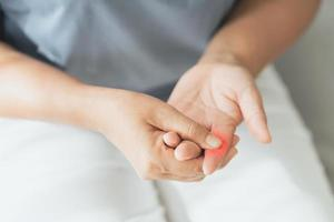 Woman suffering from hand and finger joint pain with red highlight. rheumatoid arthritis, carpal tunnel syndrome, gout. Health care and medical concept. photo