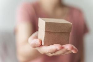 Close up of woman hands holding a small gift box. Small present box in the woman hands. photo