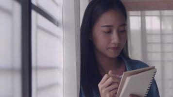 Young businesswoman writing in notebook at home video