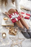 Cozy Woman legs with christmas socks and gifts. photo