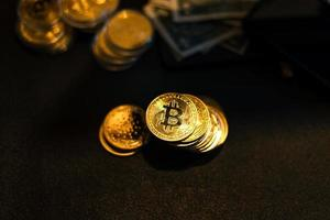 Bitcoin is placed on a desk in front of a computer graph photo