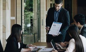 El gerente de proyecto hace una presentación para un equipo creativo joven y diverso en la sala de reuniones de una agencia. los colegas se sientan detrás de la mesa de conferencias y discuten foto