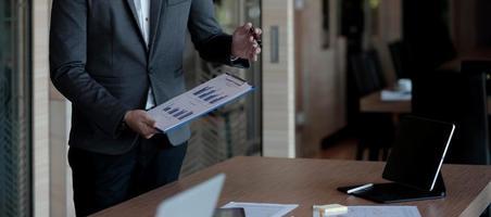 La gente de negocios que usa la computadora para analizar y discutir la situación de los datos de marketing en línea en la sala de reuniones. foto