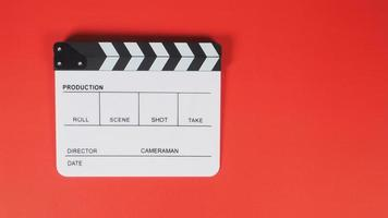 Clapperboard or movie slate. it use in video production ,film, cinema industry on red background. photo