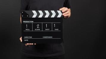 La mano sostiene el tablero de aplausos o la pizarra de películas con escritura en uso numérico en la producción de video y la industria cinematográfica sobre fondo negro. foto