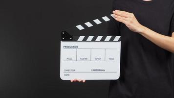 La mano sostiene el tablero de aplausos blanco o el uso de la pizarra de películas en la producción de video y la industria cinematográfica sobre fondo negro. foto