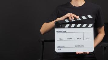 La mano de la mujer sostiene el tablero blanco de la palmada o el uso de la pizarra de la película en la producción de video y la industria cinematográfica sobre fondo negro. foto