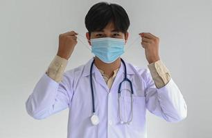 Medical professional in a lab gown with a stethoscope is wearing a medical mask, straight front photo. photo