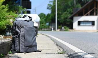 Backpack with headphones placed on the side of the road while waiting for a trip, Travel concept. photo