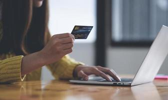Young woman using laptop computer and holding credit card, Online shopping concept, Credit card online payment. photo