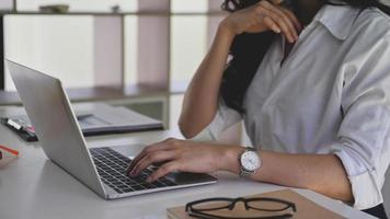 mujer de negocios que usa la computadora portátil para buscar información mientras trabaja desde casa. foto