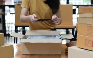 una mujer que vende un producto en línea utiliza un teléfono inteligente para tomar una foto del producto en la caja.