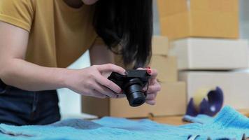 mujer joven usa una cámara para tomar fotografías de productos y publicarlos a la venta en línea. foto