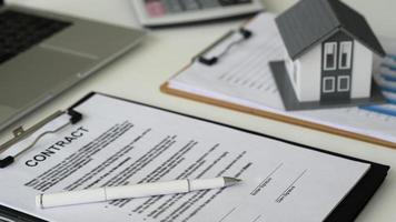 bolígrafo con documentos para firmar contrato de construcción de casa con modelo de casa y portátil, concepto de bienes raíces, primer plano. foto
