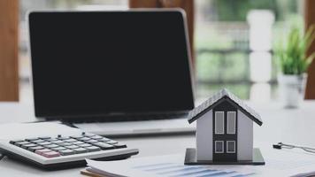 casa modelo pone un documento gráfico con una calculadora y una computadora portátil, concepto de negocio inmobiliario, compraventa de viviendas. foto