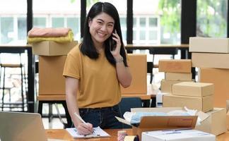 mujer vendedora en línea llama al teléfono y toma notas y toma pedidos con una sonrisa. foto