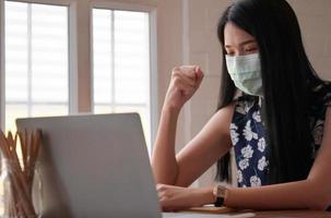 Woman in medical mask raising her fist with laptop on desk while working from home, Work from home. photo