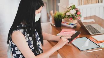 mujer que usa una máscara médica está usando un teléfono inteligente con una tableta, computadora portátil y equipo de oficina en el escritorio. foto