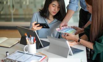El equipo de diseñadores gráficos está mirando una tabla de colores para diseñar un proyecto con una computadora portátil y una tableta en el escritorio. foto