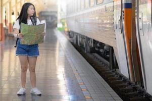A young woman with a map stands on the platform, staring at the train. photo