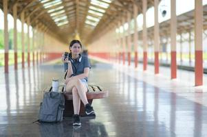 A foreign teenage girl waits for a train at the platform to travel. photo
