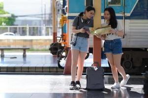 Two teenage girls plan a train trip to the platform for a trip. photo