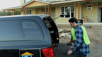 Los trabajadores de la construcción obtienen herramientas de los logotipos de empresas falsas de camiones. video
