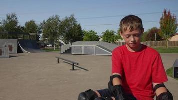 jongen krijgt helm op, bereidt zich voor op skaten in het park video