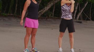 dos mujeres en la playa estirándose y preparándose para correr. filmado en rojo épico para una resolución de alta calidad de 4k, uhd, ultra hd. video