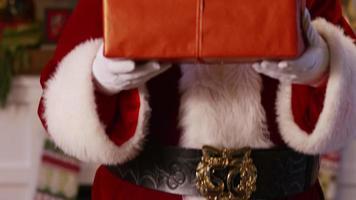 de kerstman gluurt achter een stapel geschenken vandaan video