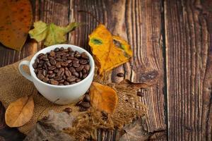 taza de granos de café y hojas secas sobre un piso de madera, hola concepto de septiembre. foto