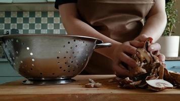 mãos colocam champignon picados frescos na peneira. mulher prepara cogumelos na cozinha de casa. estilo de vida ecológico, alimentos orgânicos saudáveis. video