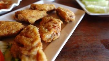 closeup 250 fps lenta alitas de pollo frito en plato en restaurante. video